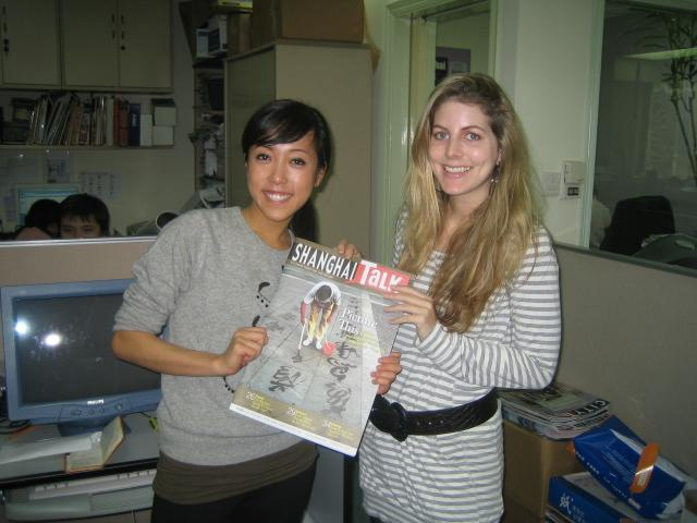A journalism intern in China holds up a magazine at her placement